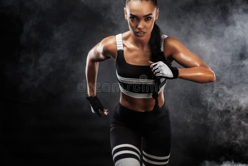 一位坚强的运动,女性短跑选手,跑在佩带在运动服、健身和体育刺激概念的日出 免版税库存图片
