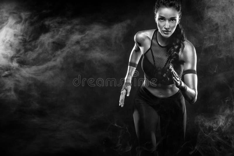 一位坚强的运动,妇女短跑选手,跑在佩带在运动服、健身和体育刺激的黑背景 免版税库存照片