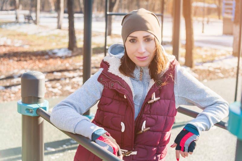 一位女孩运动员的画象一个帽子有手套的和一件温暖的背心的在户外锻炼操场旁边在a的冬天 图库摄影
