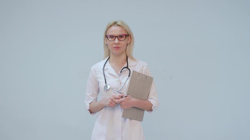 一位女性医生的画象有白色外套和听诊器微笑的调查的照相机 库存图片