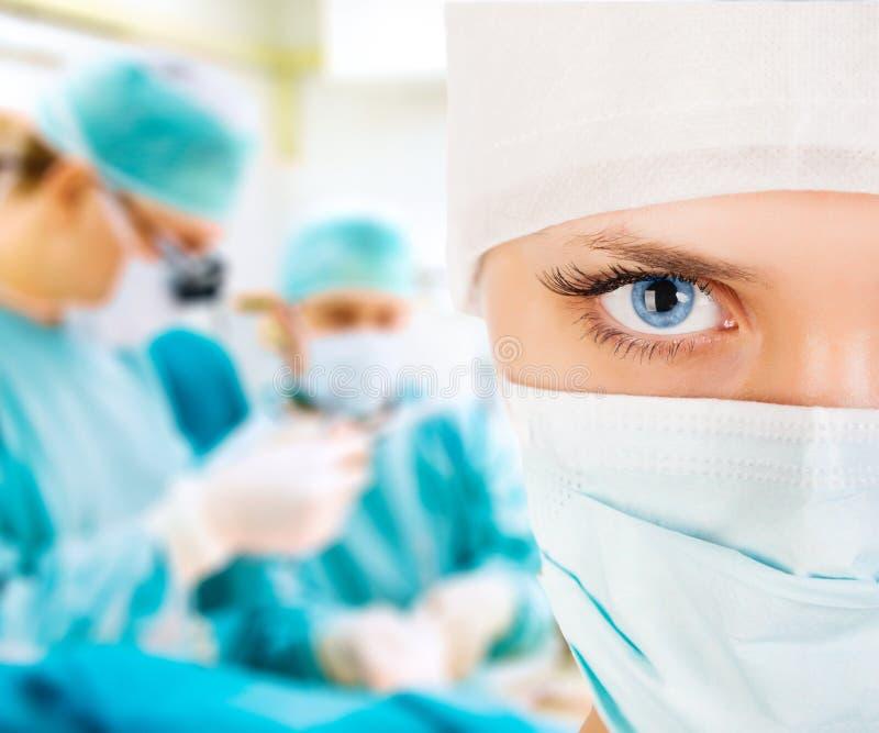 一位女性外科医生的特写镜头有他的队的 免版税库存照片