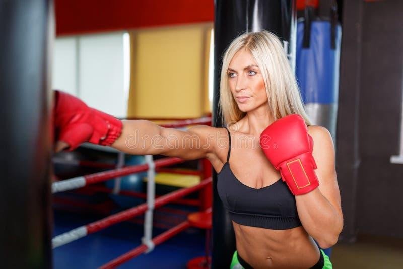 一位女性拳击手在戴着红色手套的健身房训练 免版税库存照片