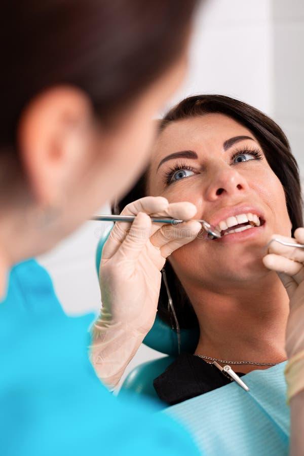 一位女性牙医审查患者的口腔有一个工具的有镜子的 一名患者的特写镜头画象与 库存照片