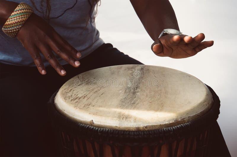 一位女性非洲音乐家播放djembe鼓 免版税库存照片