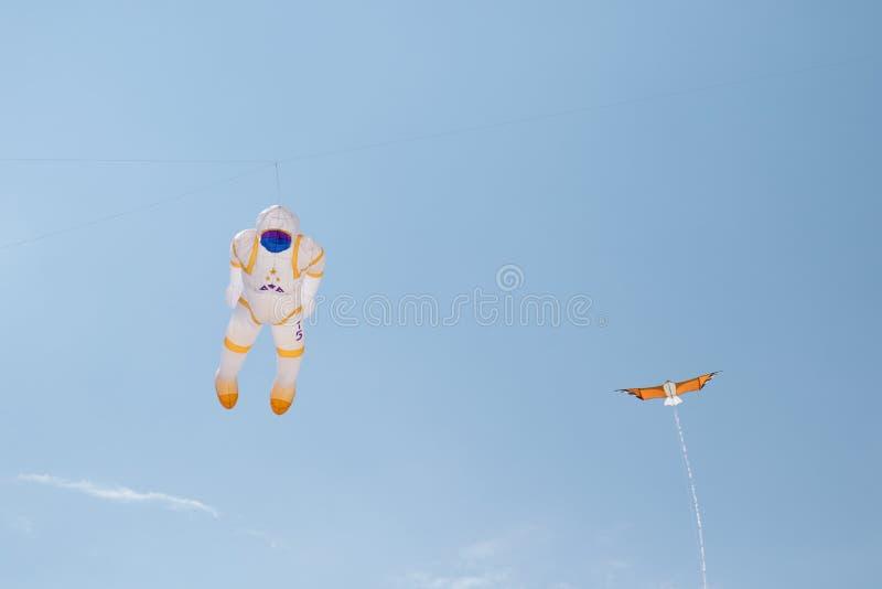 一位宇航员和一只小的龙风筝在风筝节日在存贮海geeste德国 库存照片