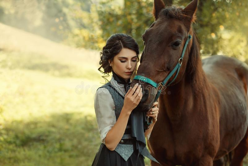 一位小姐葡萄酒礼服的,有柔软的和充满喜爱拥抱她的马 一种古老,收集的发型, a 免版税库存图片