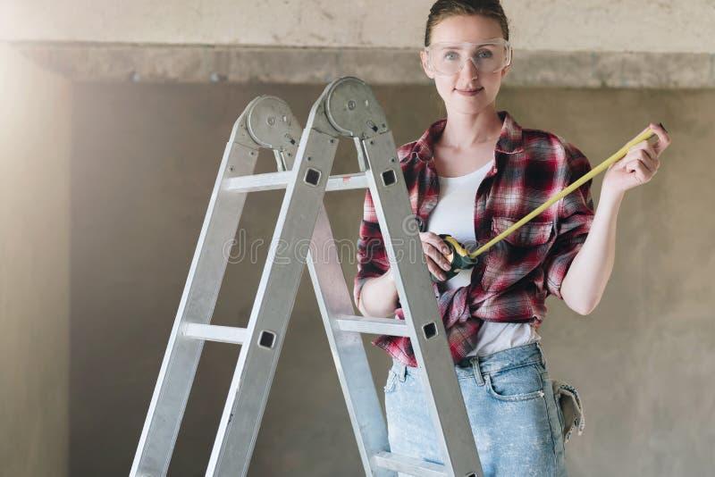 一位少妇建造者,穿戴在格子花呢上衣,蓝色牛仔裤和建筑玻璃,在活梯站立 免版税库存图片