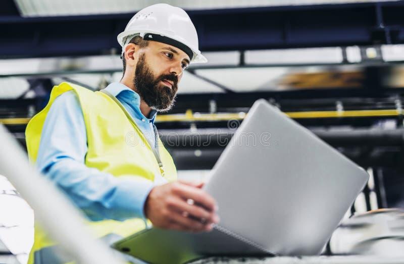一位工业人工程师的画象有膝上型计算机的在工厂,运作 免版税库存图片