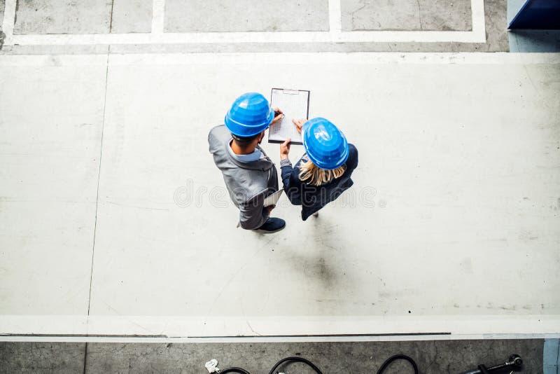 一位工业男人和妇女工程师的一张顶视图有剪贴板的在工厂 免版税库存照片