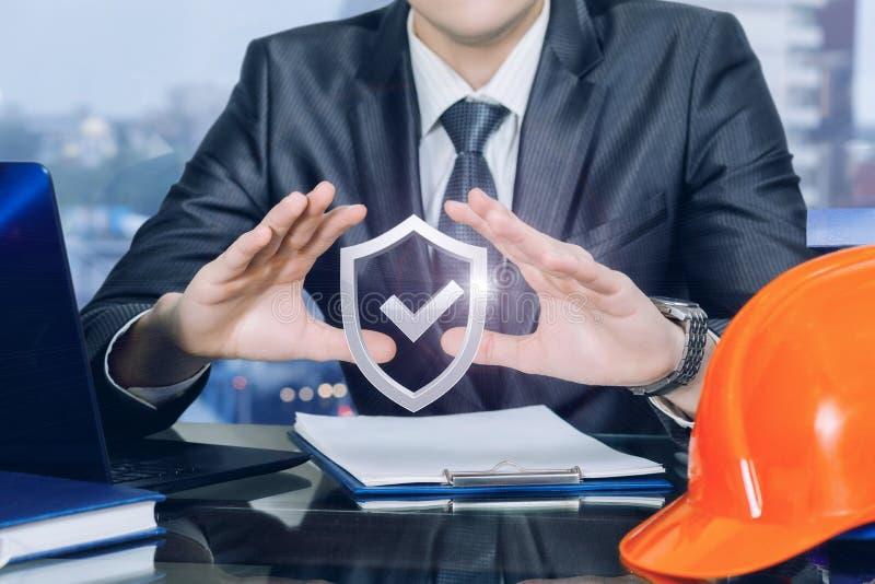 一位工程师用他的在防护位置的手在盾标志下 图库摄影