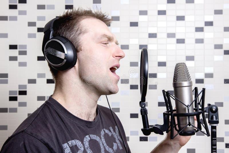 一位年轻人歌手和岩石音乐家在耳机的一台演播室电容传声器唱歌在录音室 库存图片