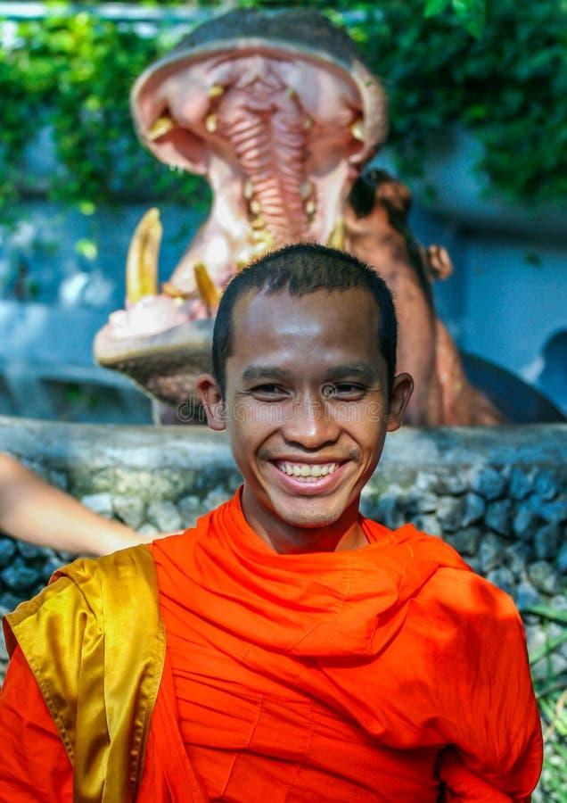 一位年轻佛教徒的画象河马的嘴背景的  免版税库存图片