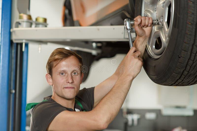 一位年轻和英俊的技工设法扭转a轮子  免版税图库摄影