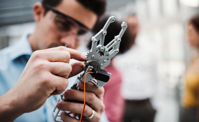 一位年轻商人或科学家有机器人手身分的在办公室,运作 免版税库存图片