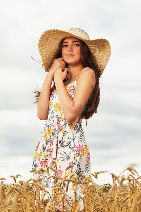 一位年轻女孩在麦田里穿着夏装。一位年轻女孩在麦田里穿着夏装。 库存照片