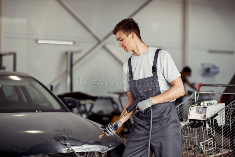 一位年轻技工洗涤一辆黑汽车在他的工作在汽车服务 免版税库存照片