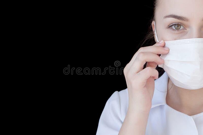 一位年轻智力医生的一张正面图一个医疗面具的在与文本空间的黑背景 免版税库存图片