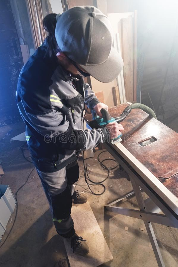 一位年轻木匠的画象与一架电子飞机一起使用在一个家庭木车间 企业想法的概念 库存照片