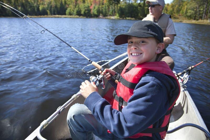 一位年轻男孩渔夫微笑,他在鱼卷 免版税库存图片