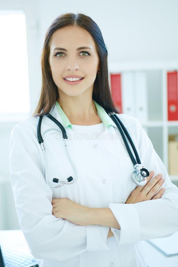 一位年轻美丽的女性医生的画象有横渡的胳膊的在办公室背景 医生等待患者 库存图片
