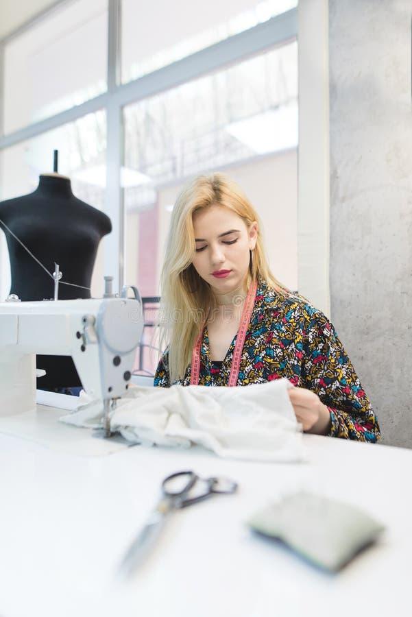 一位年轻裁缝的画象与一块布料一起使用在工作场所在一台缝纫机附近 库存图片