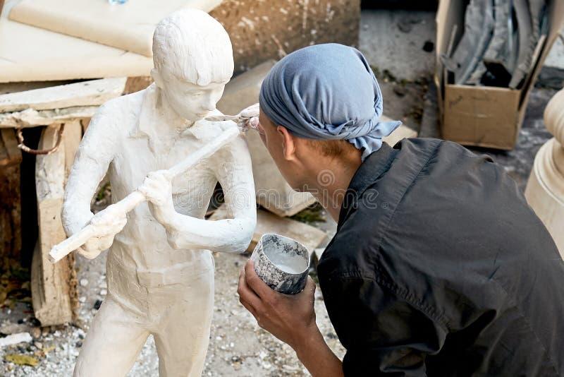 一位年轻雕刻家做雕塑白色膏药 免版税库存照片
