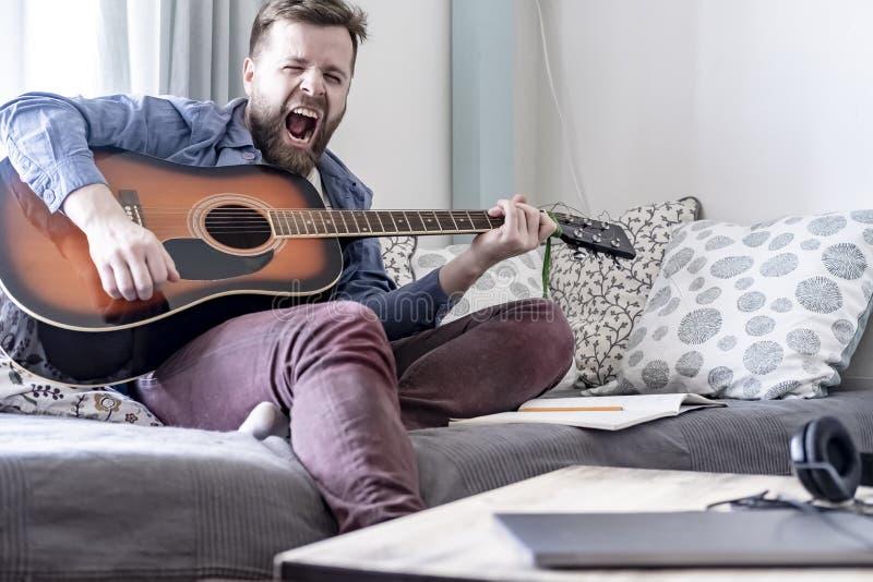 一位年轻,英俊的男性作曲家弹一把声学吉他和唱响他自己的构成歌曲,坐一个沙发,在a 免版税库存照片