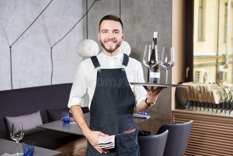 一位年轻,英俊的白种人侍者站立在有一个盘子的餐馆内部在他的手、两块玻璃和胜利卷上  免版税库存图片