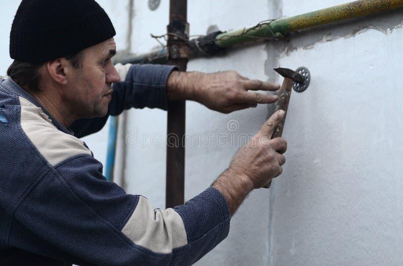 一位年长工作员堵塞定缝销钉入在聚苯乙烯泡沫塑料墙壁的塑料伞登上 免版税图库摄影