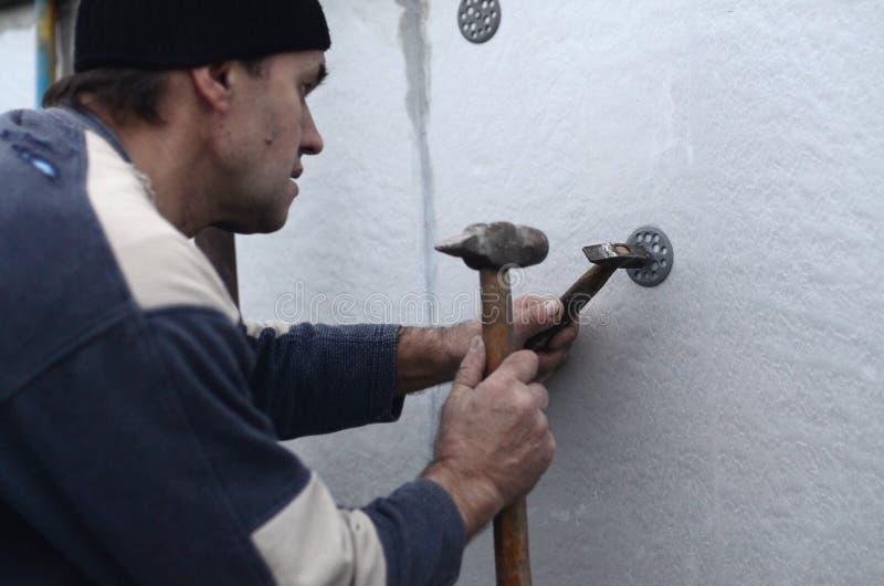 一位年长工作员堵塞定缝销钉入在聚苯乙烯泡沫塑料墙壁的塑料伞登上 免版税库存照片
