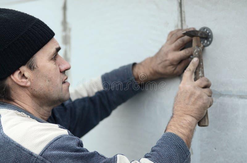 一位年长工作员堵塞定缝销钉入在聚苯乙烯泡沫塑料墙壁的塑料伞登上 图库摄影