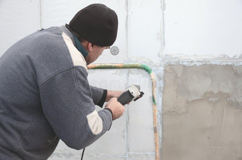 一位年长工作员操练在聚苯乙烯泡沫塑料墙壁的一个孔塑料加强的定缝销钉的随后设施的 创建 库存图片