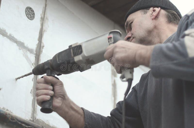 一位年长工作员操练在聚苯乙烯泡沫塑料墙壁的一个孔塑料加强的定缝销钉的随后设施的 创建 免版税库存图片