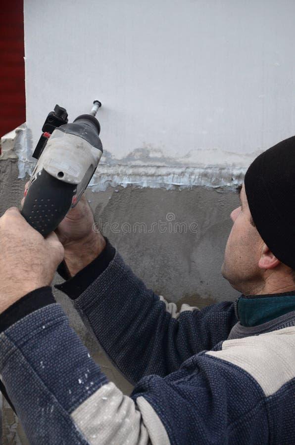 一位年长工作员操练在聚苯乙烯泡沫塑料墙壁的一个孔塑料加强的定缝销钉的随后设施的 库存照片
