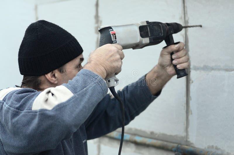 一位年长工作员操练在聚苯乙烯泡沫塑料墙壁的一个孔塑料加强的定缝销钉的随后设施的 免版税库存照片