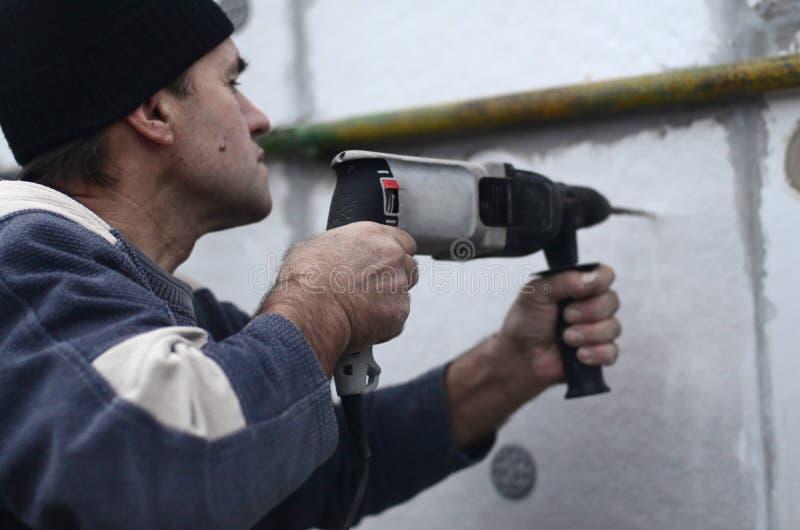 一位年长工作员操练在聚苯乙烯泡沫塑料墙壁的一个孔塑料加强的定缝销钉的随后设施的 免版税库存图片