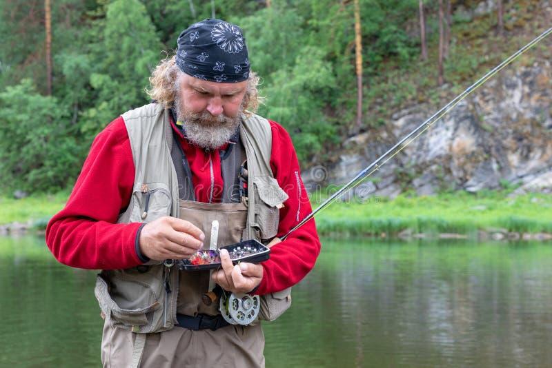 一位年长渔夫有钓鱼或实心挑料铁杆的和有滑车的鱼箱子的 免版税库存图片