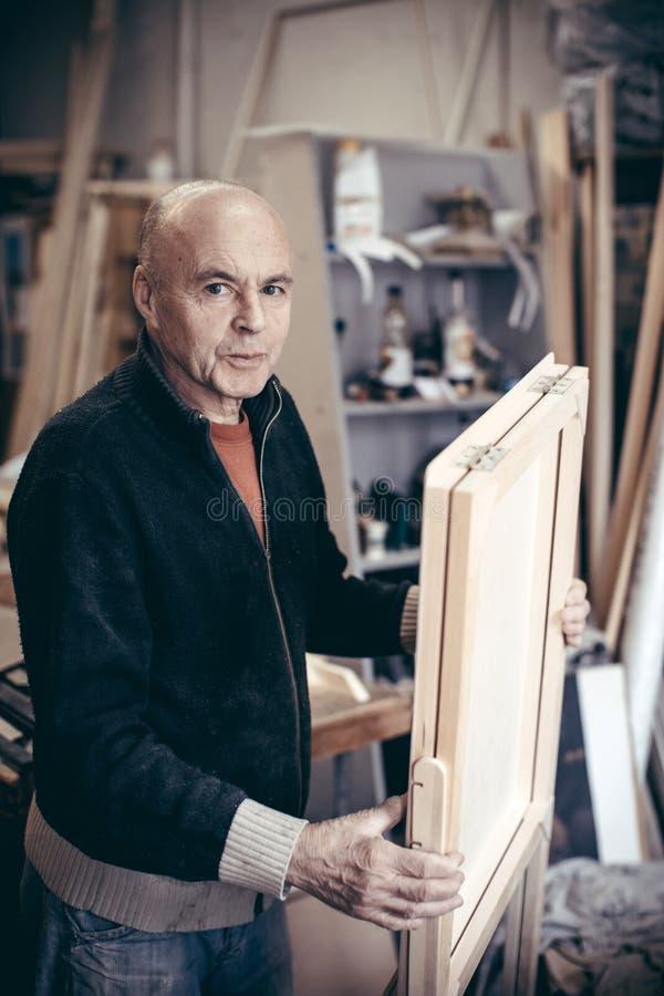 一位年长老练的木匠的画象有微笑的与f 免版税图库摄影