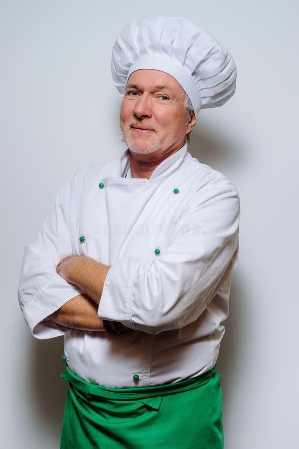 一位微笑的厨师的画象灰色背景的 友好,快乐,吸引人厨师 图库摄影