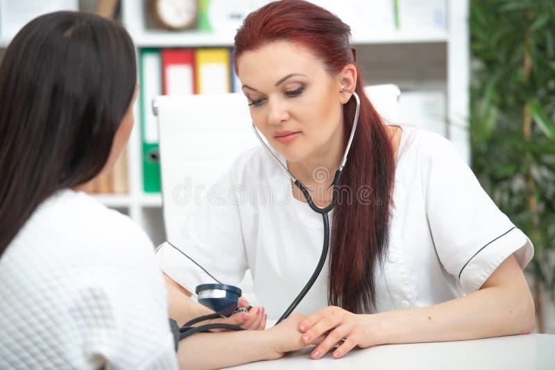一位微笑的友好的医生采取他的办公室和措施压力的一名患者 妇女给医嘱 库存照片