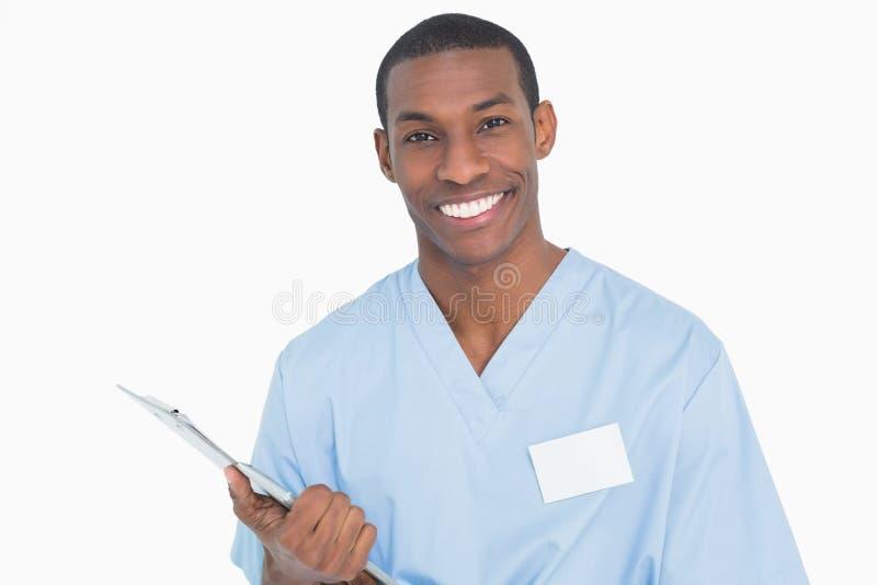 一位微笑的男性外科医生的画象有剪贴板的 库存照片