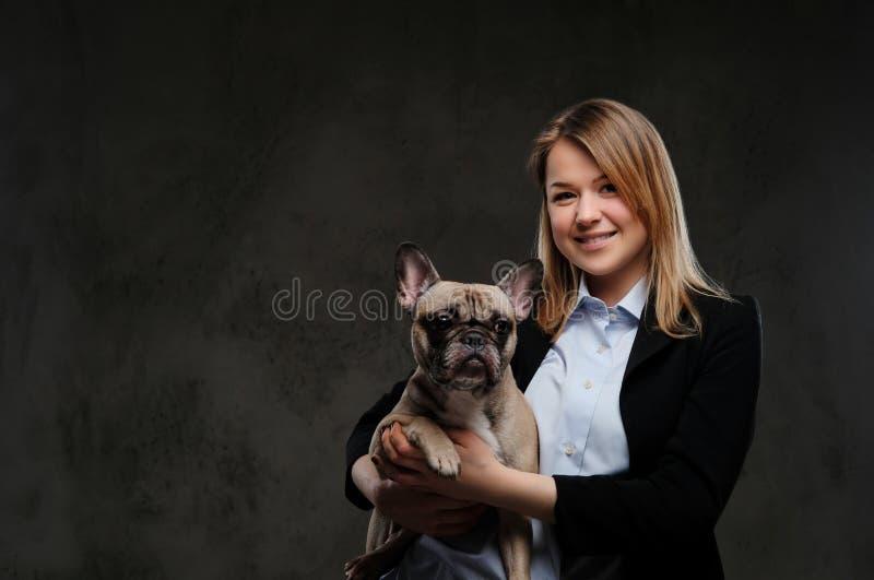 一位微笑的白肤金发的妇女交配动物者的画象拿着她逗人喜爱的哈巴狗 隔绝在黑暗的织地不很细背景 库存照片