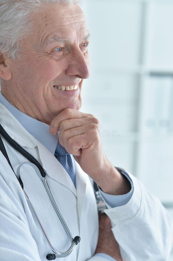 一位微笑的资深男性医生的画象 库存图片