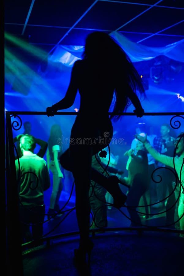 一位性感的舞蹈家的剪影一家俱乐部的在夜党的阶段 免版税库存图片