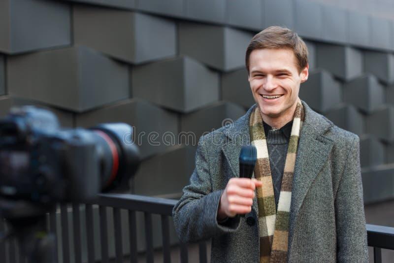 一位愉快的男性记者带领关于照相机的一个报告在街道上 库存照片