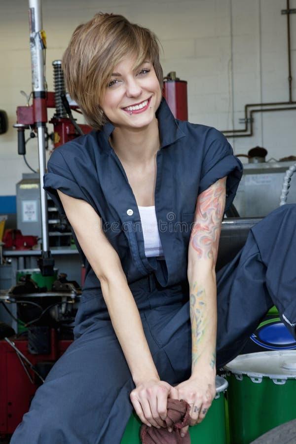 一位愉快的年轻女性技工的画象坐油桶在汽车车间 免版税库存照片