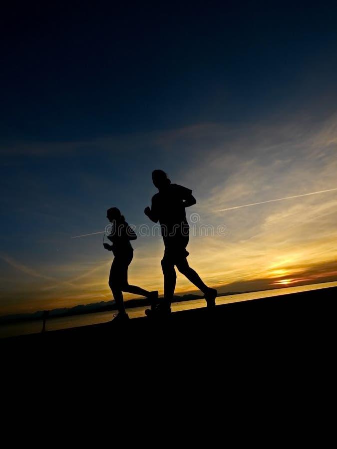 一位慢跑者的剪影在日出的 库存图片