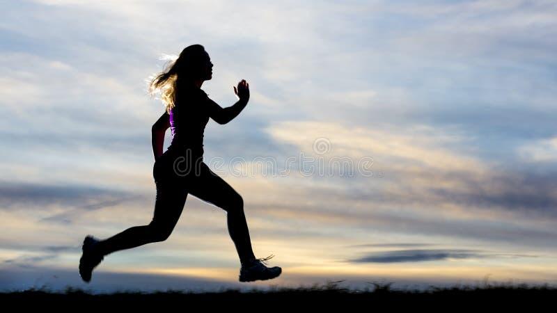 一位慢跑者的剪影在日落的 免版税库存图片