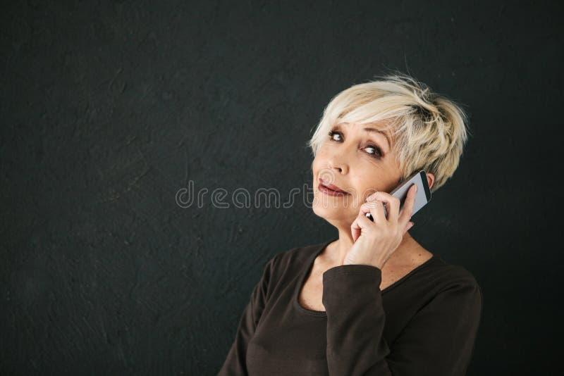 一位成功的正面年长女性顾问谈判手机 人使用之间的通信现代 库存图片