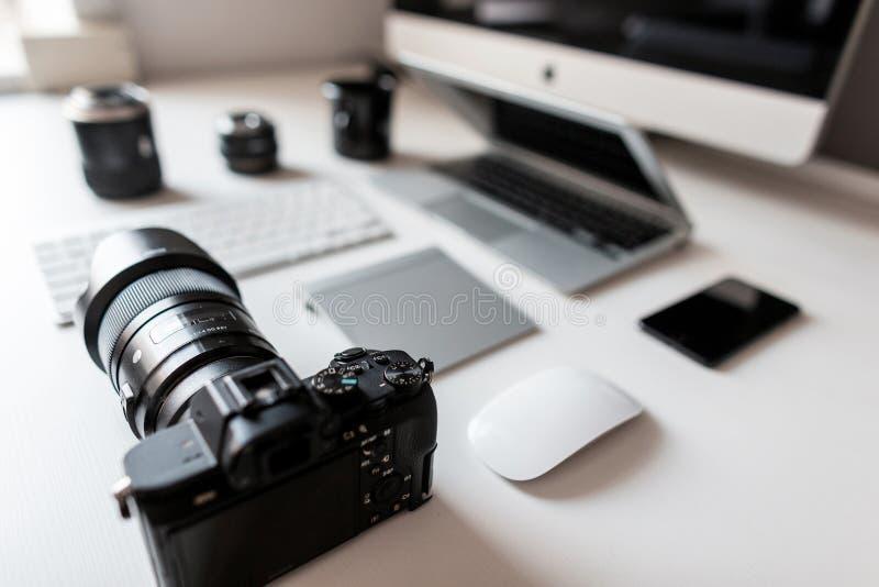 一位成功的设计师的白色桌面有一台膝上型计算机的有与一台现代专业照相机的一只老鼠的与有膝上型计算机的一个键盘 库存图片